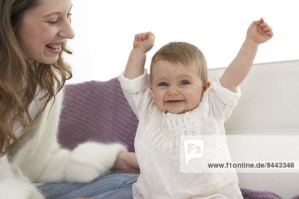 Lächelndes Mädchen mit ausgestreckten Armen neben ihrer Mutter