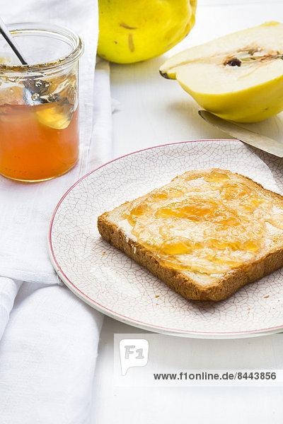 Quitten (Cydonia oblonga)  selbstgemachtes Quittengelee und Toastscheibe auf weißem Holztisch