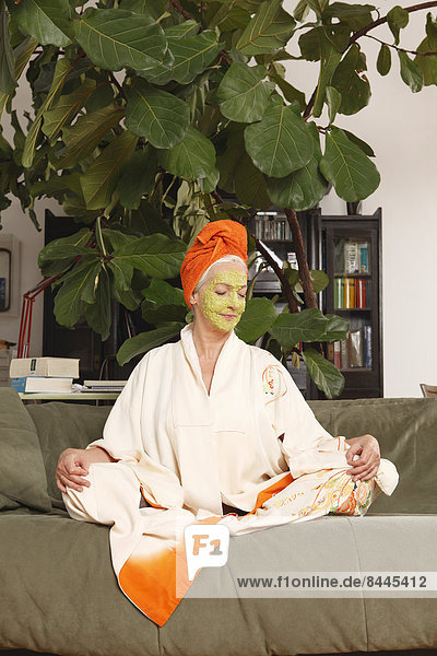 Senior woman with face mask sitting on sofa
