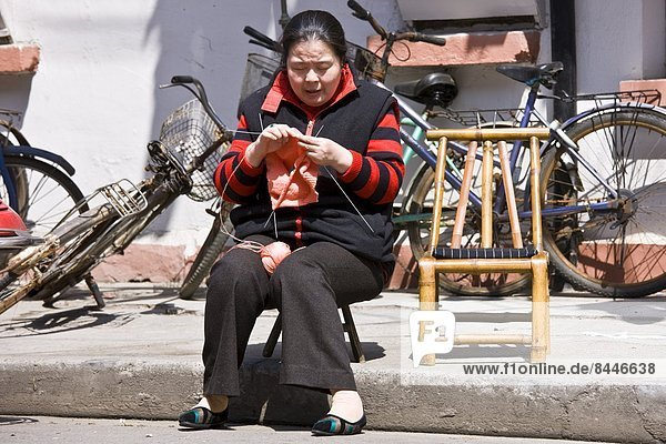 Woman sits knitting in Zi Zhong Road  old French Concession Quarter in Shanghai  China
