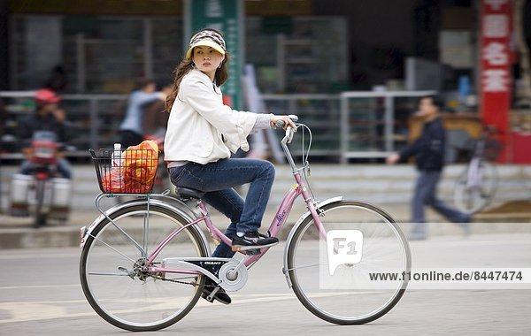 Young woman on a bicycle in Yangshuo street  China