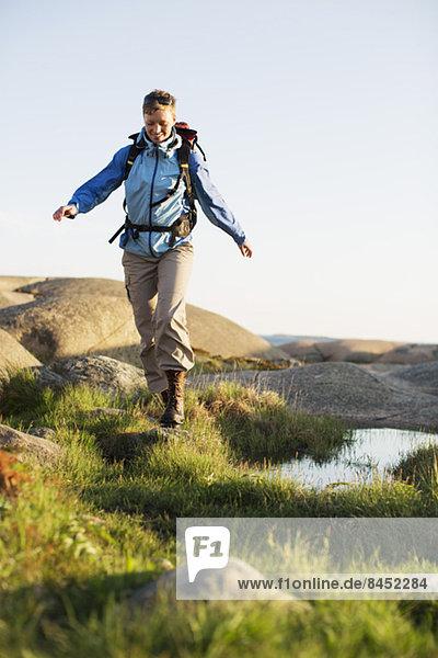 Volle Länge der weiblichen Backpackerin beim Wandern im Freien