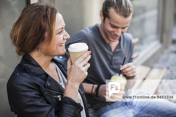 Fröhliche Frau trinkt Kaffee in Einwegbecher mit Mann auf Bank auf dem Bürgersteig