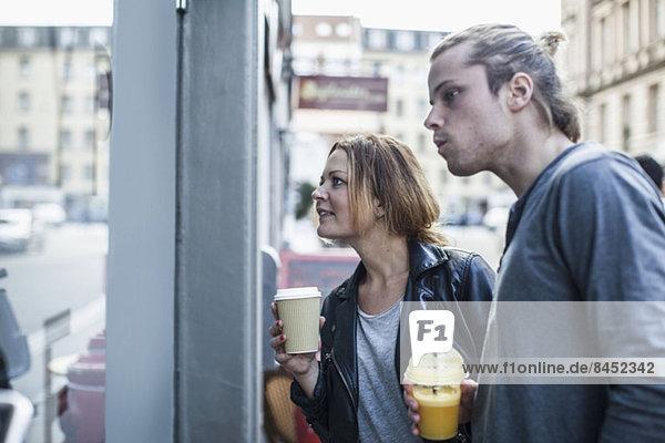 Paar mit Einwegbechern beim Schaufensterbummel