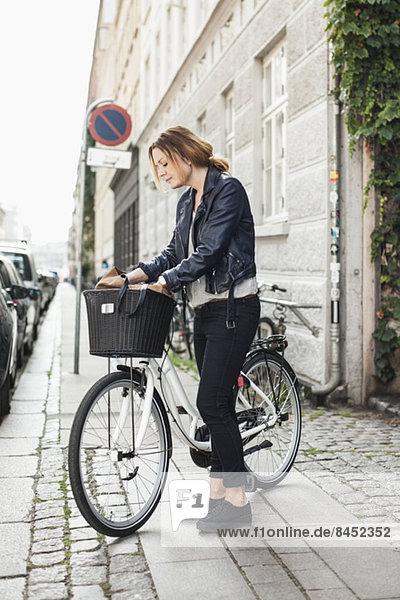 Mittlere erwachsene Frau auf der Suche nach etwas in der Tasche im Fahrradkorb an der Straße