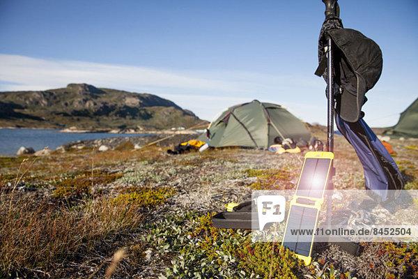 Solarladegerät mit Zelt im Hintergrund auf dem Campingplatz
