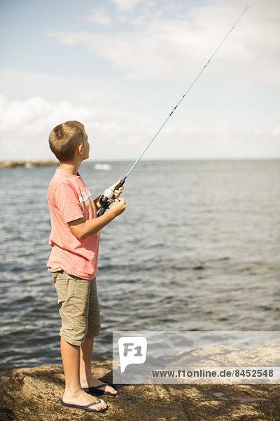 Volle Länge der Jungen beim Angeln am Seeufer