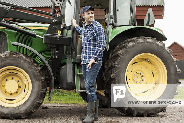 Volle Länge des Landwirts mit dem Traktor auf dem Bauernhof