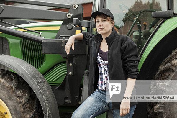 Porträt einer selbstbewussten Bäuerin am Traktor