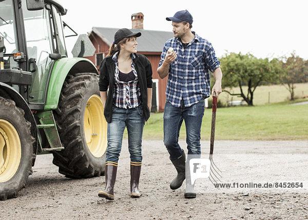 Volle Länge des Bauernpaares  das mit dem Traktor läuft