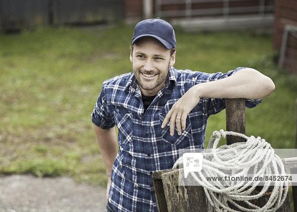 Lächelnder Bauer schaut weg  während er sich auf das Geländer auf dem Bauernhof stützt.