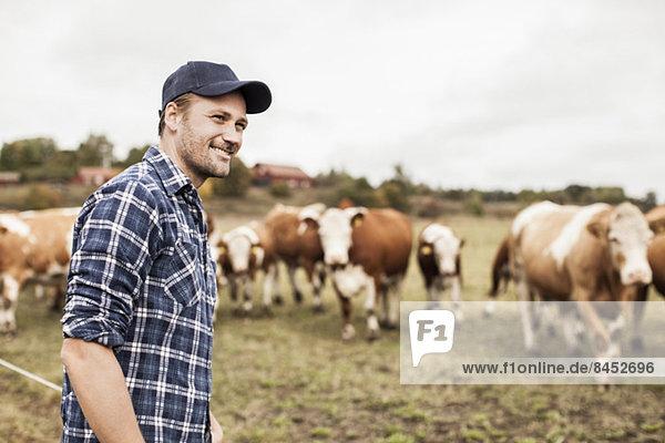 Lächelnder Bauer schaut weg auf das Feld  während die Tiere im Hintergrund grasen.