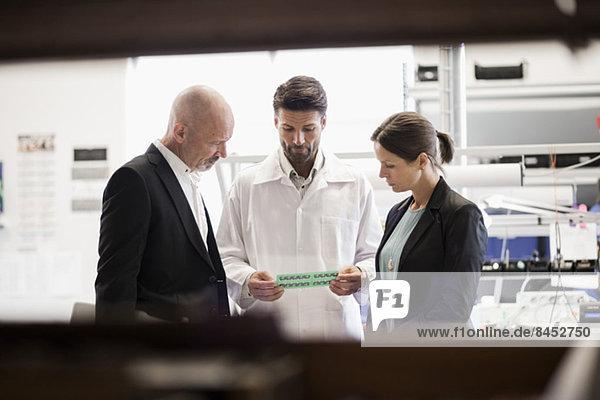 Ingenieur im Gespräch mit Geschäftsleuten in der Fabrik