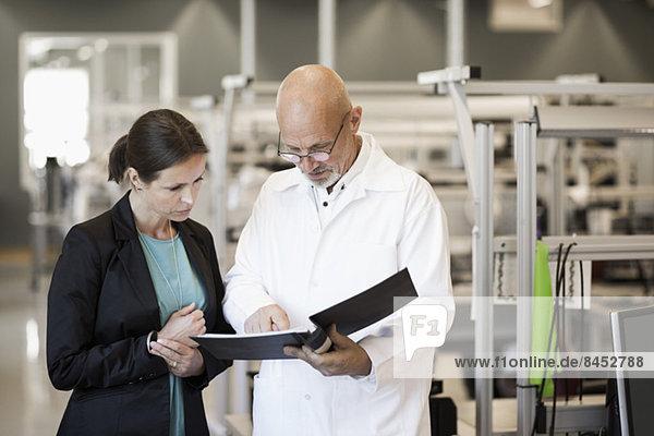Ingenieur und Geschäftsfrau bei der Suche nach Akten in der Industrie
