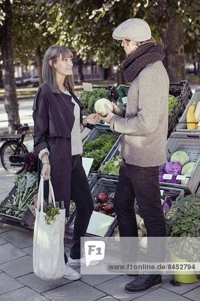 Volle Länge des Verkäufers  der Gemüse der Frau am Marktstand zeigt.