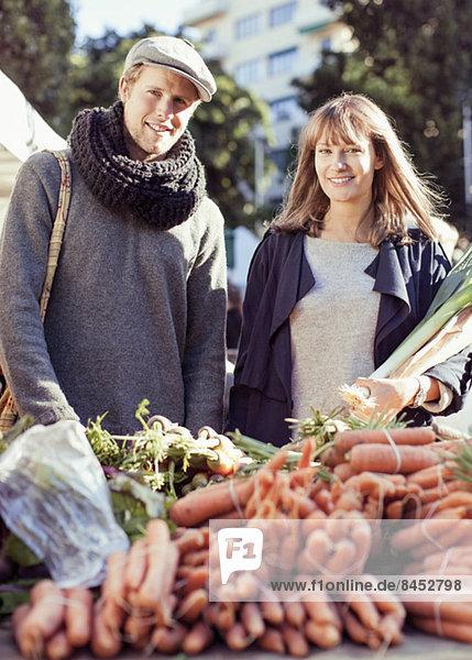Porträt eines Paares beim Gemüsekauf auf dem Markt