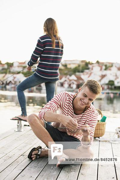 Glücklicher Mann  der die Angelrute einstellt  während die Frau im Hintergrund am Pier fischt.