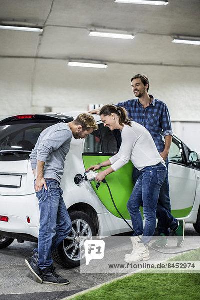 Männliche Freunde mit Frau beim Aufladen des Elektroautos an der Tankstelle