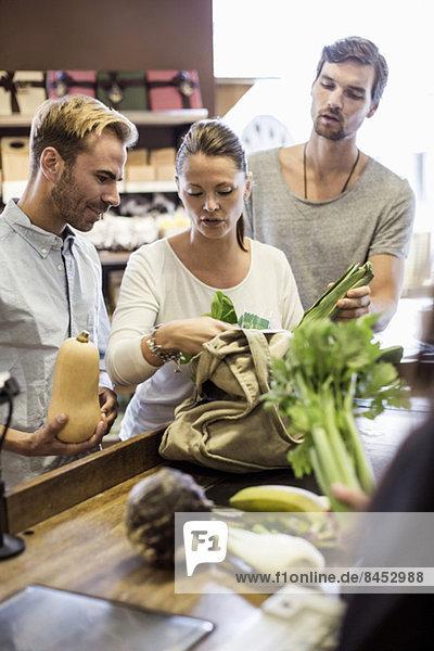 Freunde diskutieren beim Gemüsekauf an der Supermarktkasse