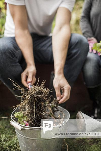 Mittelteil des Mannes  der Schmutz im Eimer im Freien hält