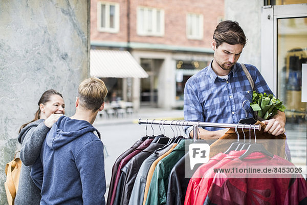 Junger Mann beim Auswählen von Jacken mit Freunden  die am Bekleidungsgeschäft vorbeigehen
