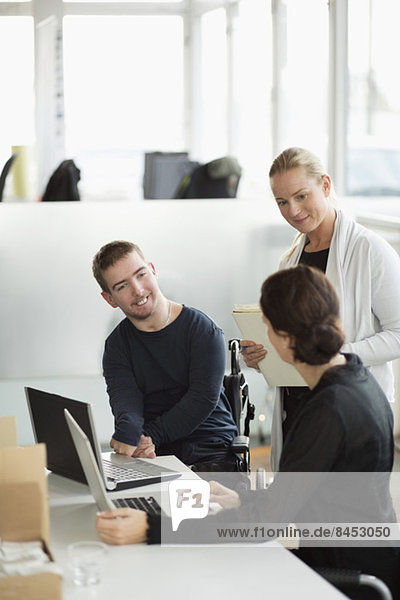 Behinderter Geschäftsmann im Gespräch mit Kolleginnen im Amt