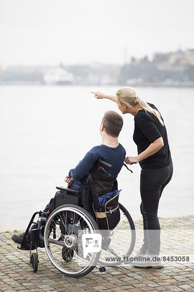 Hausmeister zeigt dem behinderten Mann im Rollstuhl am See etwas.