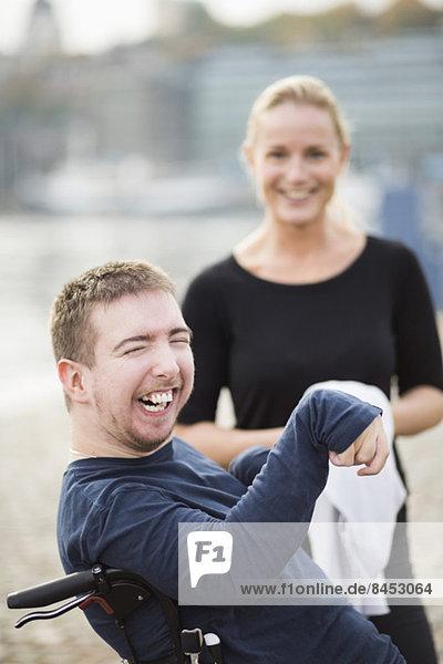 Behinderter Mann im Rollstuhl lacht durch Hausmeister im Freien