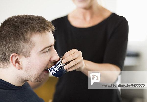 Mittelteil der Hausmeisterin  die den behinderten Mann zu Hause mit Kaffee füttert.