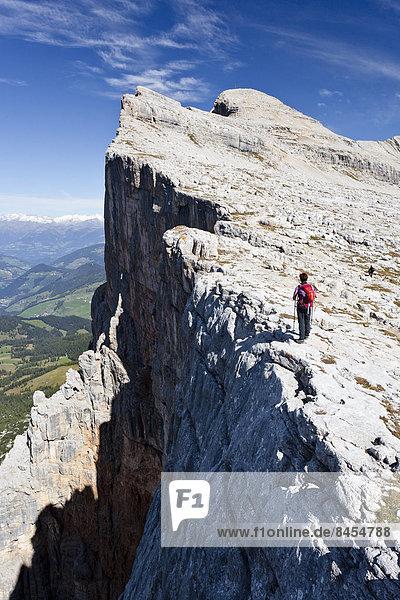 Bergsteigerin auf der Kreuzkofelscharte beim Aufstieg auf den Heiligkreuzkofel über den Heiligkreuzkofelsteig im Naturpark Fanes-Sennes-Prags  hinten der Heiligkreuzkofel  unten das Gadertal  Dolomiten  Südtirol  Italien
