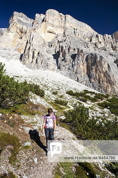 Bergsteigerin beim Abstieg über den Heiligkreuzkofelsteig vom Heiligkreuzkofel  hinten  in der Fanesgruppe im Naturpark Fanes-Sennes-Prags  Gadertal  Dolomiten  Südtirol  Italien