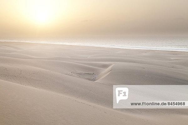 Sonne im Dunst des Meeres über der Dünenlandschaft am Strand Praia de Chaves  an der Westküste der Insel Boa Vista  Kapverden