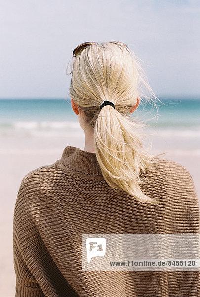 Eine blonde Frau mit blonden Haaren  die von der Küste aufs Meer hinaussieht.