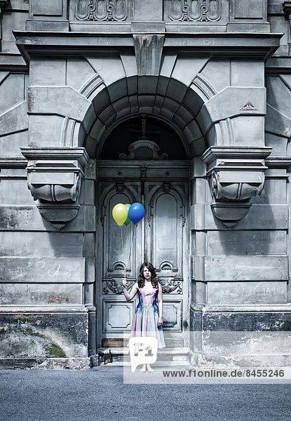 Mädchen mit Luftballons vor altem Tor Mädchen mit Luftballons vor altem Tor