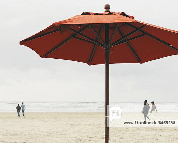 Ein großer Sonnenschirm am Strand von Manzanita  am Pazifischen Ozean in Oregon.