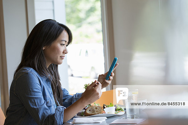 A woman eating a salad  and checking her phone.