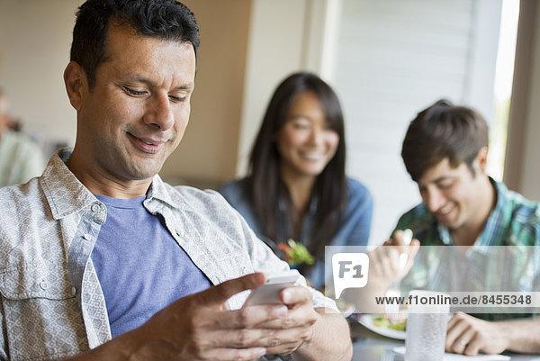 Drei Personen saßen an einem Café-Tisch.