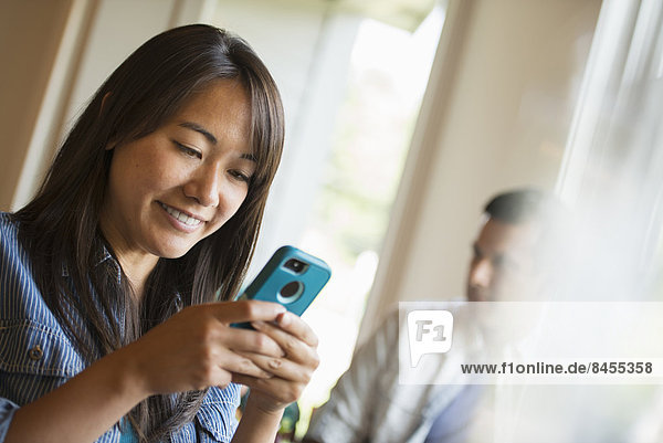 Eine Frau überprüft in einem Café ihr Smartphone.