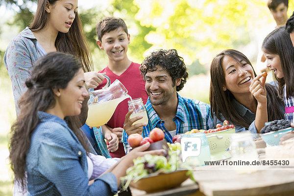 Erwachsene und Kinder um einen Tisch in einem Garten.