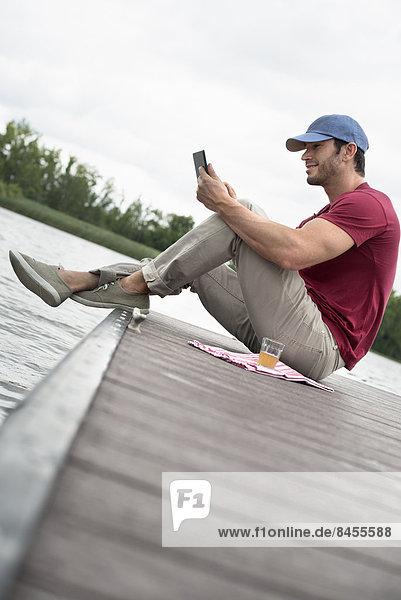 Ein Mann sitzt auf einem Steg an einem See und benutzt ein digitales Tablett.