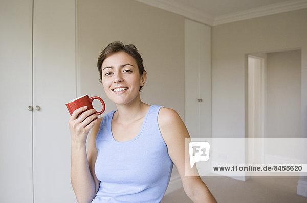Eine Frau mit blauem Oberteil  sitzend  einen roten Porzellanbecher haltend.