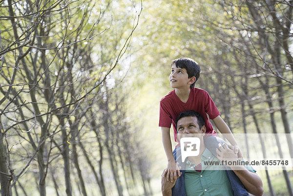 Ein Junge mit einem Huckepack  der auf den Schultern eines Mannes reitet.