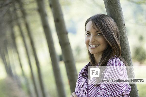 stehend Frau lächeln Baum Allee
