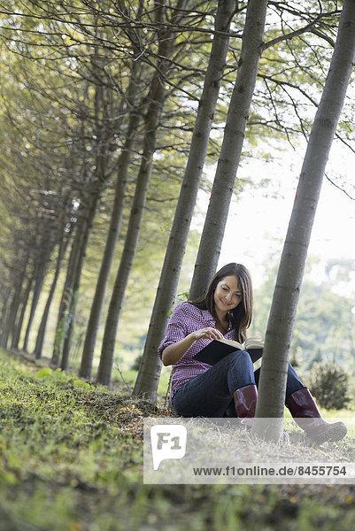 sitzend, Frau, Buch, Baum, unterhalb, Taschenbuch, vorlesen