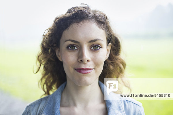 Eine junge Frau in einer ländlichen Landschaft  mit vom Wind gelocktem Haar  lächelnd.