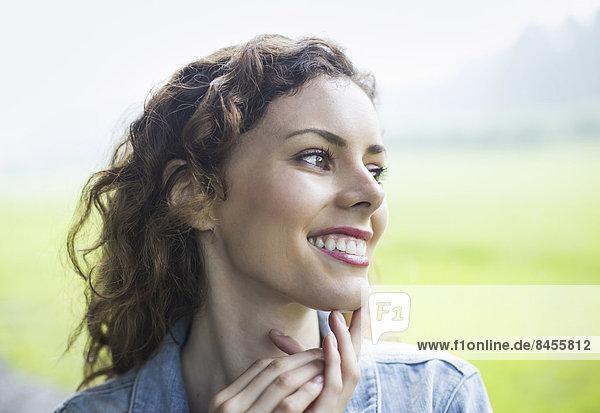 Eine junge Frau in einer ländlichen Landschaft  mit windgewelltem lockigem Haar. In die Ferne blickend.