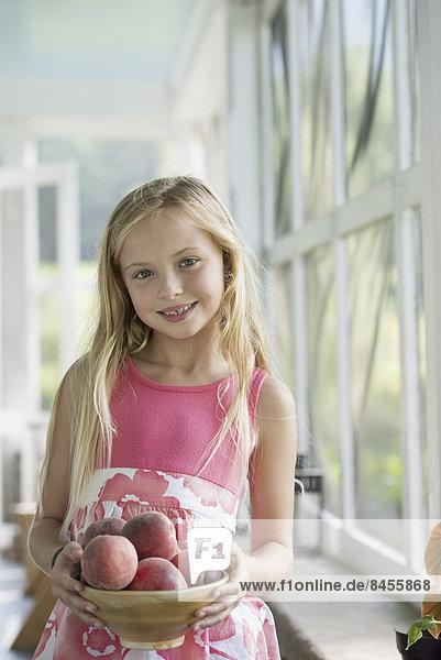 Ein junges Mädchen hält einen Arm voller frischer Pfirsiche.
