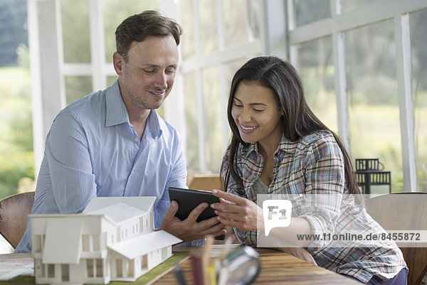 A man and woman looking at a digital tablet  designing a house.