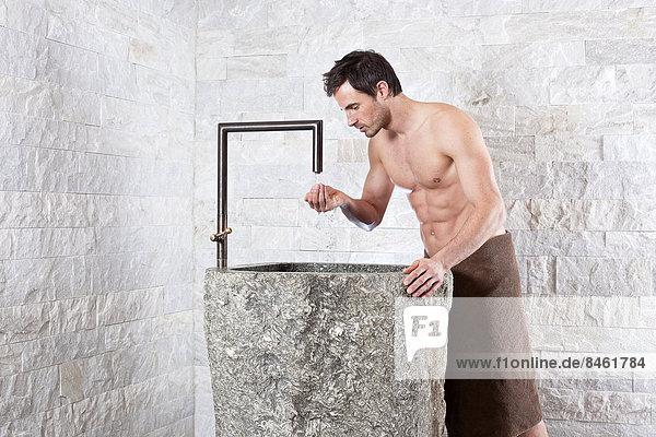 Mann mit freiem Oberkörper steht an einem Trinkwasserbrunnen in einer Wellnessanlage Mann mit freiem Oberkörper steht an einem Trinkwasserbrunnen in einer Wellnessanlage
