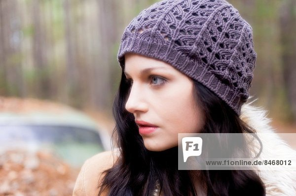 Profile portrait of a 20 year old brunettte woman wearing a knit cap looking away from the the camera outdoors.
